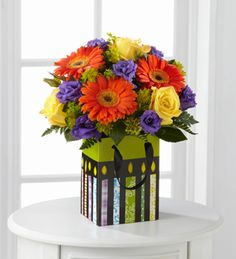 The FTD® Perfect Birthday Gift Bouquet is bright and cheerful bouquet set to get the celebration started! Bright yellow roses, orange gerbera daisies, and purple lisianthus create a brilliant splash of color arranged amongst lush greens and placed in a bright birthday bag displaying candles in every shade. A wonderful way to show you care on his big day.