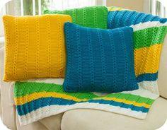 Material: – Fio Cisne D'Primera (nov. 40 g): 4 nov. na cor: 0000B (branco), 10 nov. na cor 00745 (verde) e 9 nov. em cada uma das cores: 00168 (amarelo) e 00736 (azul); – Ag. para tricô…