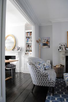 That chair is fantastic! I like the pop of blue on the white and dark, wide floorboards.