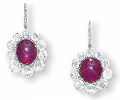 A PAIR OF STAR RUBY EAR PENDANTS Each suspending a star ruby weighing 11.50 and 9.71 carats, within a rose-cut diamond surround, to the diamond-set hook, mounted in 18k white gold