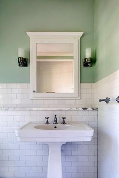 Charming white and green bathroom features wall clad in white subway tiles on the lower walls and green upper walls lit by two sconces mounted on either side of a white framed medicine cabinet positioned over a marble ledge fixed above a white pedestal bathroom sink.