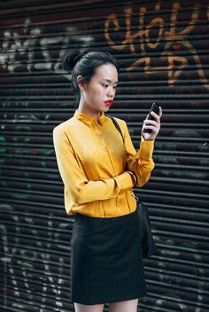 Portrait of a young asian businesswoman using a mobile phone on the street. by Eduard Bonnin