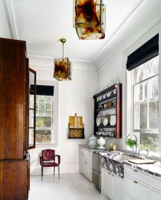 Kitchen with marble farm sink, and antique plate rack. Design by Windsor Smith. Elle Decor.