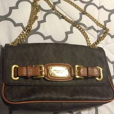Michael Kors monogram leather purse Michael Kors purse in great condition. It's a monogram leather purse with gold hard ware. It has a double Chain, which can be worn over the shoulders. The inside of the purse,has credit card slots and a pocket with a zipper. Michael Kors Bags Shoulder Bags