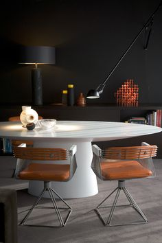 Dining Room - Contemporary modern dining space with round table with pedestal and uber modern leather & metal designer chairs.....an artistic expression & highly original.