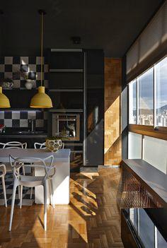 Cozinha preta e branca com piso de madeira
