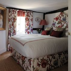 This tiny bedroom in the country cottage of Paolo Moschino and Philip Vergeylen obeys one of the cardinal rules of small space design. Don't feel that just because the space is small the furniture or patterns have to be. In this space the bed takes up the majority of the room, and a bold red floral used over bed and window gives a punch of character which nods to the English country cottage tradition. Adding light to rooms with low ceilings is crucial