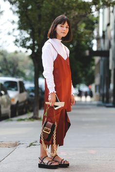 For fall, layer your go-to slip dress over a ruffled turtleneck. #refinery29 http://www.refinery29.com/2016/09/120553/nyfw-spring-2017-best-street-style-outfits#slide-48