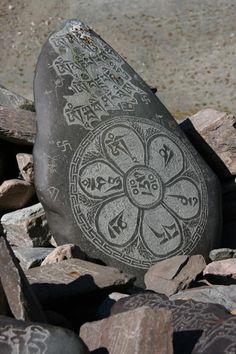 Carved mani stone balances on top of a mani wall along the trail in Zanskar.