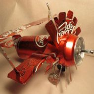 Made entirely from six Yuengling Black & Tan Beer cans, clear silicone calk, wire, and two Yuengling bottle caps for wheels. The propeller spins smoothly and easily with a fan or breeze. Made to hang from a wire (outside) or string (inside). Relatively durable, will survive falls but may be become dented with poor handling.