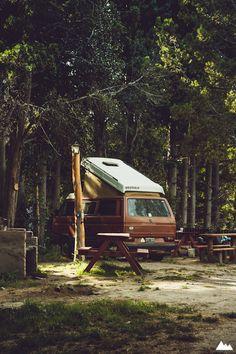 vw camper van - hood up in the woods