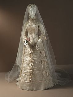 Silk satin wedding dress with bows and pleated ruffles, American, c. 1878.