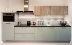Deze keuken is uitgevoerd in de nieuwe kleur fjord blauw. Een nieuwe kleur uit het assortiment van Pronorm uitvoerbaar in zowel hoogglans als mat. Het fjord blauw is hier gecombineerd met olm grijs, welke terugkomt in de wandkasten.