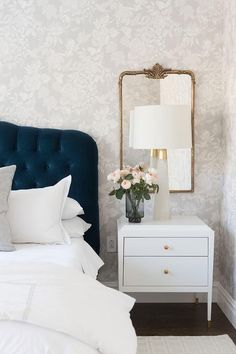 A gold French ornate mirror hangs from an accent wall covered in gray floral wallpaper over a white nightstand lit by a white and gold lamp. - A gold French ornate mirror hangs from an accent wall covered in gray floral wal. Accent Wall Bedroom, White Bedroom, Modern Bedroom, Mirror Bedroom, Wall Mirror, Bedroom Wallpaper Luxury, Wall Paper For Bedroom, Bedroom With Wallpaper Accent Wall, Grey Wallpaper Accent Wall