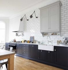 good job mixing styles.  black range, amazing hood. porcelain sink. subway tiles New Kitchen, Updated Kitchen, Kitchen Reno, Kitchen Remodel, Two Tone Kitchen Cabinets, Kitchen And Bath, Kitchen On A Budget, Kitchen Ideas, Kitchen Paint