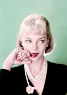 Model wearing a black jacket and pearl necklace, 1957.