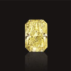 FANCY VIVID YELLOW DIAMOND RING The cut-cornered rectangular modified brilliant-cut diamond weighing 36.05 carats, mounted in 18 karat gold.