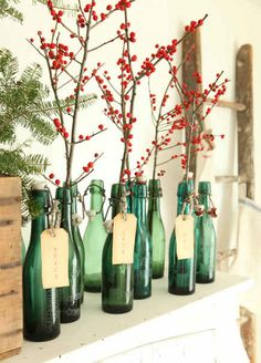 berry branches in green-glass bottles as mantel decor