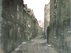 Lower Fore Street in Lambeth, London c. 1860's.  Uneven cobbles, walls jutting out and leaning as if about to collapse, and is that a costermonger's barrow at the end of the alley?