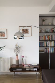 Der Hooper Couchtisch mit Ablage in Walnuss mit der Bow Bogenlampe im Zuhause von MADE Kundin Sophie in Berlin. | Made Unboxed