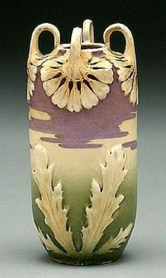 Category:  pottery & porcelain   Type:  teplitz   Origin:  Austria   Year:       A Teplitz vase. Four looped openwork leaf-form handles above purple and green base with large leaves, red Teplitz mark on base.
