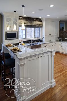 I usually don't like white kitchens, but I like the marble/maple/white combination in this one.