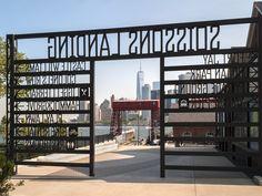 The transparent signage frames a view of Lower Manhattan.