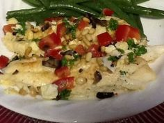 Thick tilapia steaks, browned in butter, covered in a feta cheese sauce, sprinkled with diced tomato, olives and toasted pine nuts, then baked and topped with lemon juice and parsley . . . light and layered with flavors!