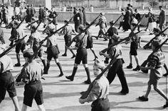 Muchachos jóvenes que desfilan en las calles de Irún, con uniformes y rifles de pega sobre sus hombros en un desfile organizado por el bvando franquista después de haber conquistado la ciudad durante la Guerra Civil española. 13 de noviembre 1936