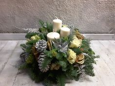 A round #Christmas #tablecentre in #silvers and #whites with three white #candles and #roses, silver #thistle, #fern and #cones, and #driedfruits. Christmas Arrangements, Christmas Flowers, Table Centers, White Candles, Fern, Centre, Bouquet, Roses, Wreaths