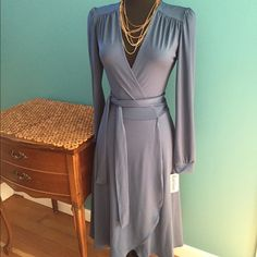 Slate blue jersey knit flattering wrap dress Sophisticated wrap dress style in easy wash and wear jersey knit. Knee length with pleated detail on back. One size fits 4-10 depending on fit preference. Clearance from my inventory of Karina Dresses. Photo of me in the dress style. I'm a 10p. Dresses Long Sleeve