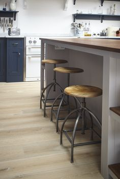 Charlie Kingham South-West London Edwardian House | A traditional kitchen with industrial highlights. A hardwood shaker style kitchen in located in south-west London. Mylands 'Bond Street' Blue hand painted finish, an island with breakfast bar (Mylands Crace) with industrial stools.