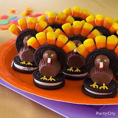 Clever cookie and candy creation  This colorful Thanksgiving confection will be the talk of the party! It's fun to share recipes and your dinner guests will love this one made from cookies, malt balls, candy corn, mini peanut butter cups and icing. Create a colorful dessert table display using an orange plate with a purple charger.