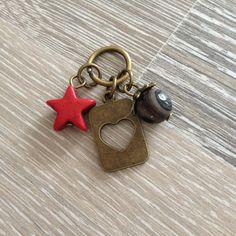 Bedel van 8mm Botswana agaat met bronzen sierkap, rode howliet ster en bronzen kaartje met hart uitdruk. Van JuudsBoetiek, te bestellen op www.juudsboetiek.nl.
