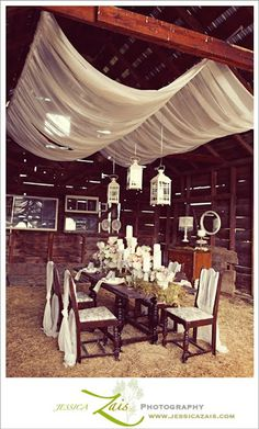 White draping would look great over the sweetheart table. I love the white candle sticks with white candles at staggered heights.