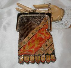 "WHITING & DAVIS Art Deco Mesh Purse. The mesh is beautifully detailed and enameled in colors of butterscotch, tangerine, black and pea green. The silvertone frame is enameled in black and has a kiss lock closure. The delicate wire chain handle drops 6"" from the top and the purse itself measures 6 1/2"" to the fringe. It is 3 1/2"" wide across the top. It has the W&D logo plate on the inside of the frame. (hva)"