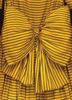 This detail of a day dress c. 1947 shows the extravagant bow. The fabric is a yellow silk grosgrain with a narrow green stripe and supported with net petticoats and a horsehair frill. The dress is by Victor Stiebel of London.