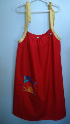 Bright red dress made in the pillowcase style but  fashioned from a material remnant.