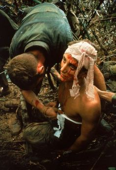 Larry Burrows. A dazed, wounded American Marine gets bandaged during Operation Prairie near the DMZ during the Vietnam War, October 1966.