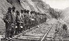 convict labor  - a work gang - black prisoners in prison stripes working on railroad tracks