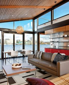 The floor-to-ceiling windows at either end of a Seattle boathouse allow light to stream through the entire 1,000-square-foot space.