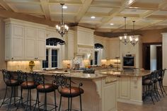 This grand-scale kitchen features creamy white cabinets, a gorgeous coffered ceiling and traditional chandeliers. Barstools line the peninsula and counter-height stools line the island, creating two spaces for quick, casual dining.