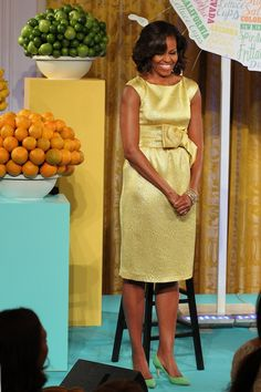 """The First Lady hosted the second Kids' """"State Dinner"""" in the East Room of the White House today, in partnership with Epicurious, the Department of Education, and the Department of Agriculture. The event recognized 54 winners of a national recipe challenge to promote healthy lunches. For the event, Mrs. O wore aMichael Korssunshine metallic silk matelasse sheath dress, last seen in October 2009, here."""