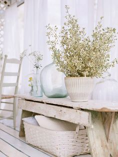 OMG LOVE THIS!! Would need some background wall color or floor a tad too much white for me as a whole but just LOVE the feel of it.  Distressed Perfection-This old workbench has been converted into a side table in the dining room, displaying flea-market vases and wildflowers. The bench was whitewashed and distressed, adding to the classic charm of this cottage-style home