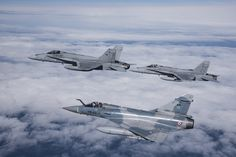 Pair of Finnish Air Force F/A - 18 Hornets in formation with French Armée de l'Air Dassault Mirage 2000.