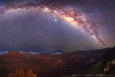 The Milky Way Over Mauna Kea, Hawaii. Since we are inside this disk, the band appears to encircle the Earth. The bright spot just below the band is the planet Jupiter. In the foreground lies the moonlit caldera of the volcano Haleakala. A close look near the horizon will reveal light clouds and the dark but enormous Mauna Kea volcano on the Big Island of Hawaii.