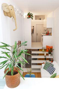 Visitamos el piso de 21 m2 de Alberto Bravo. Cabeza de elefante de esparto de Cestería Sagón, maceta de mimbre de los 80 de la madre de Alberto, mesillas de colores de Habitat, cojines de rayas de Casa Josephine, sofá Erktop de Ikea.