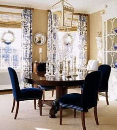 Simply adorned for the holidays, this dining room features a white-painted antique breakfront that showcases blue-and-white porcelain: http://www.bhg.com/christmas/indoor-decorating/set-your-holiday-table-with-style/?socsrc=bhgpin121214indigoelegance&page=13