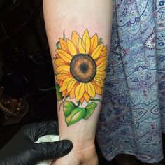 Solo sunflower tattoo on the arm. This beautiful sunflower is the highlight of the design as it is inked along and is painted with bright and bold colors to stand out.