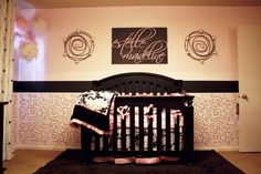 elegant nursery ideas - split wall with border and spirals, poms hanging in the corner, and pretty wall candler holders.